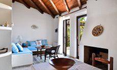 Heller Wohnbereich mit Sofaecke und sardischem Kamin