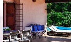 Überdachte Terrasse mit Esstisch aus Granit und Blick zum Pool