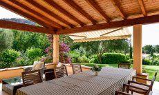 Großer, überdachter Esstisch auf der Terrasse
