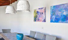 Esstisch mit eleganten Korblampen und gemalten Bildern in  Villa Campidano 20
