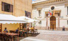 Das Rathaus von Alghero mit sardischer, italienischer, europäischer und katalanischer Flagge
