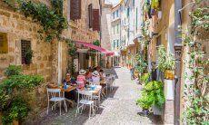 Schmale, autofreie Gass in Alghero mit Tischen eines Restaurants auf der kopfsteingepflasterten Staße