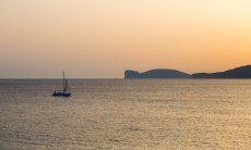 Das Meer bei Alghero beim Sonnenuntergang mit einem Segelboot und der Silhouette vom Capo Caccia