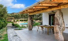 Terrasse mit Bambusverkleidetem Dach auf Granitsäulen und Blick auf den Pool und die Berge