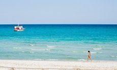 Frau läuft am weißen Strand von La Cinta vor dem hellblauen Meer mit einem weiß und roten Boot