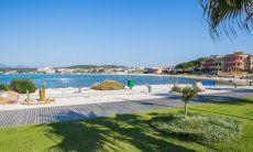 Stadtstrand mit Rasen und weißem Sand beim Hafen von Golfo Aranci