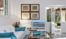 Elegantes Sofa mit Sofatisch und TV im Wohnzimmer mit Blick auf die Veranda und den Garten