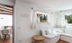 Sofaecke im Wohnzimmer mit Blick in Grüne und auf die Terrasse von Su Faru 3 Pula