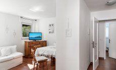 Wohzimmer mit Sofa, Esstisch, TV und Zugang zu den Zimmern von Su Faru 3 Pula